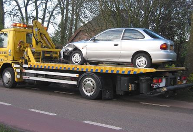 A wrecked silver sedan towed by a yellow flatbed tow truck after an accident